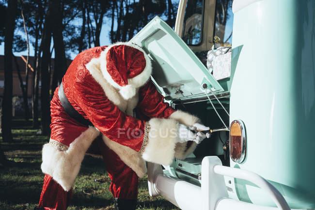 Человек в красно-белом костюме Санта-Клауса осматривает двигатель старинного зеленого фургона в солнечный день — стоковое фото