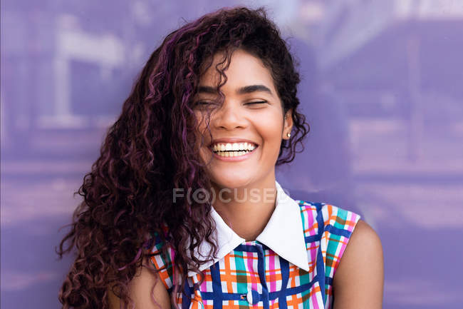Portrait of charming young ethnic young woman with curly hair with closed eyes laughing near purple glass wall — Stock Photo