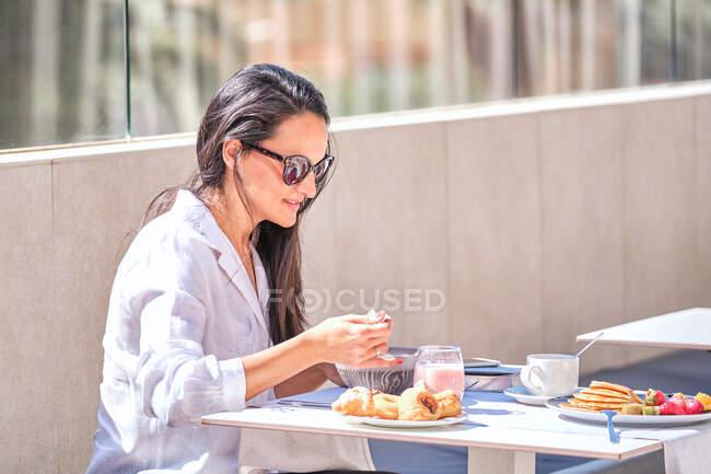 Senhora muito amigável em óculos de sol sentado à mesa servida no terraço iluminado ao sol aberto e comer iogurte rosa enquanto espera pelo parceiro — Fotografia de Stock