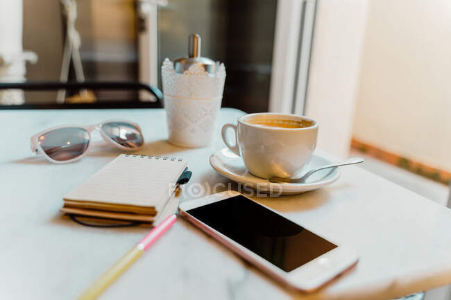 Білі смартфони і чашка з кавою на мармуровому столі в кафе з маленькими блокнотами і стильними сонцезахисними окулярами. — стокове фото