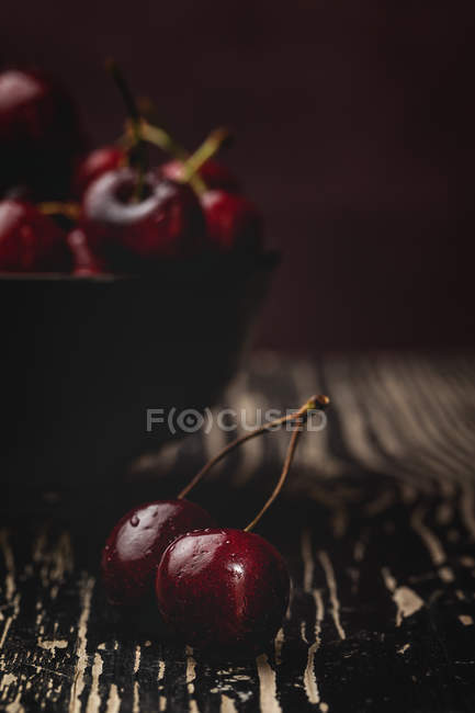 Tasty ripe cherries in on rustic wooden background with bowl — Stockfoto