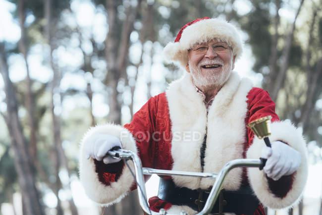 Старший чоловік у костюмі Діда Мороза сидить на циклі, дзвін дзвін і дивлячись на камеру — стокове фото