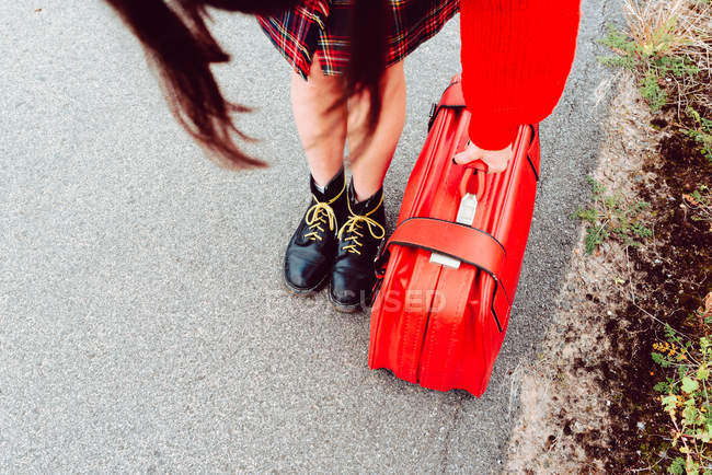 Woman in stylish boots with red suitcase standing on road — Stockfoto