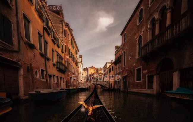 Gondola di uccello dorato galleggiante tra case colorate — Foto stock