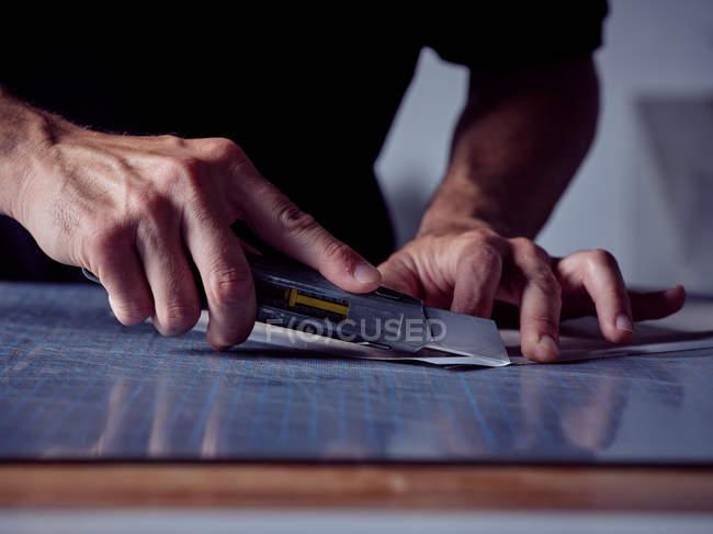 Mani di uomo professionale che taglia fogli di carta con speciale coltello affilato sul tavolo di lavoro — Foto stock