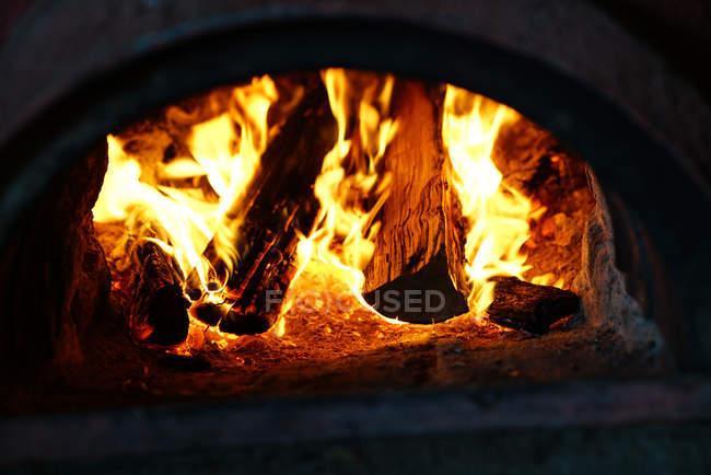 Hot bright burning fire with in oven in darkness — Stock Photo