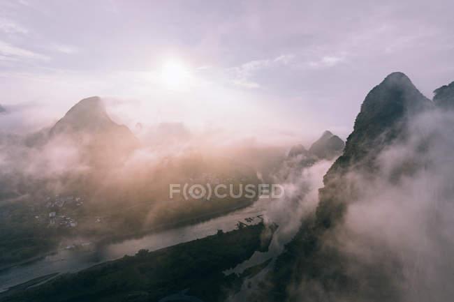 Vista aérea del río tranquilo y montañas oscuras rocosas en la niebla de la mañana con nubes que fluyen bajo el cielo brillante y el sol - foto de stock