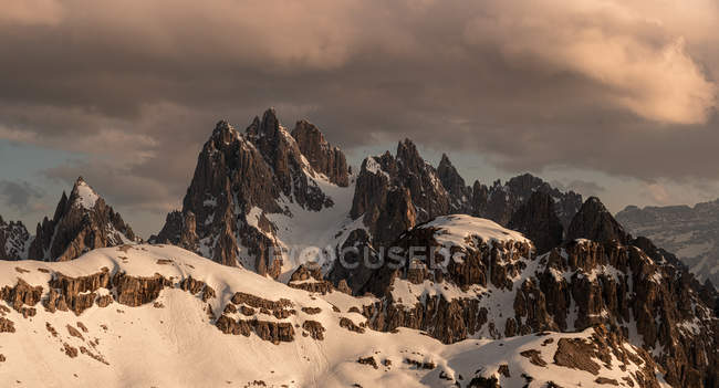 Majestic landscape of snowy rocky peaks under heavy dark clouds in gray sky in Dolomites, Italy — Stock Photo