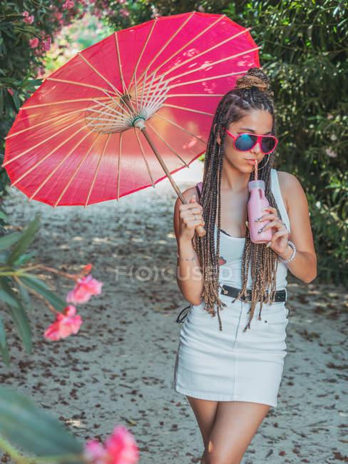 Sottile giovane donna in abito estivo con ombrello bere bevanda vicino alberi in fiore — Foto stock