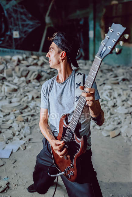 Musician playing electric guitar in abandoned place — Stock Photo