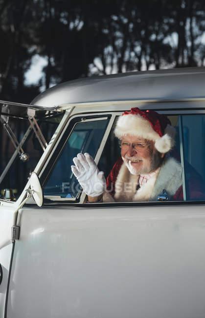 Веселий старший чоловік в костюмі Діда Мороза сидить у старому Ван і розмахуючи рукою від відкритого вікна — стокове фото