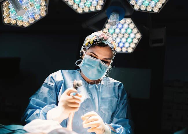 Von unten ernsthafter junger Arzt in Schutzmaske und Mütze, der mit Instrumenten und Erntekrankenschwester operiert — Stockfoto