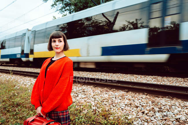 Stylish woman in red sweater with red suitcase looking along while fast train riding on railway behind back — Stock Photo