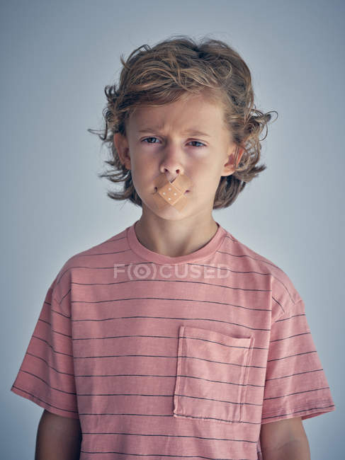 Curly thoughtful kid keep silence with plaster on mouth and looking at camera — Stock Photo