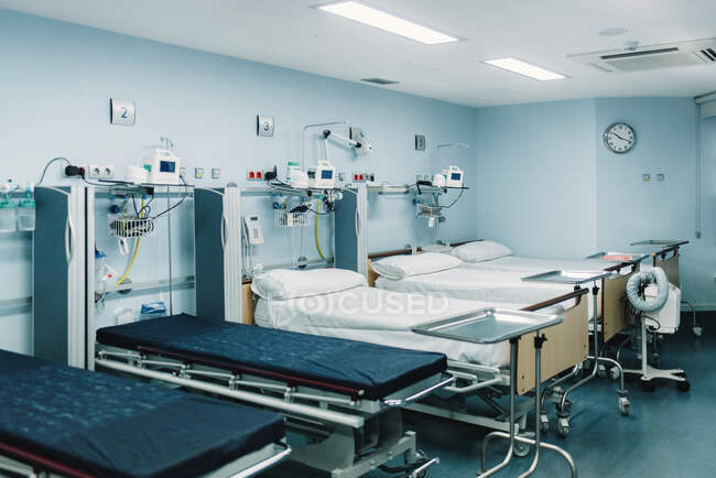 Equipped intensive care unit with beds made up for patients and metal trays for medical needs — Stock Photo