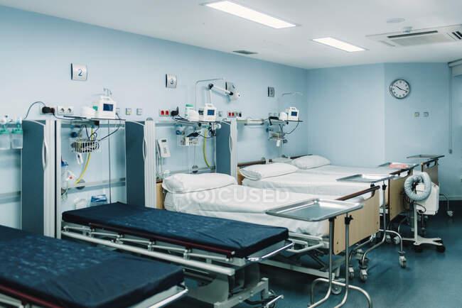 Ausgestattete Intensivstation mit Betten für Patienten und Metalltabletts für medizinische Bedürfnisse — Stockfoto