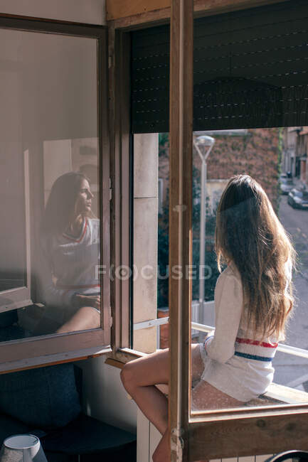 З боку погляд струнка жінка сидить на підвіконні в квартирі і дивиться у м'якому світлі — стокове фото