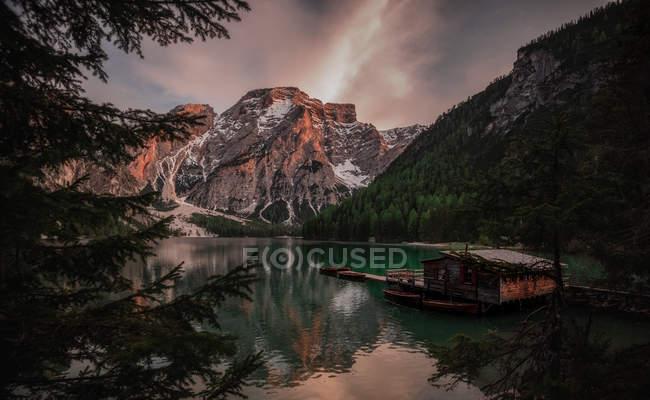 Casa flutuante cercada com as montanhas no lago sereno — Fotografia de Stock