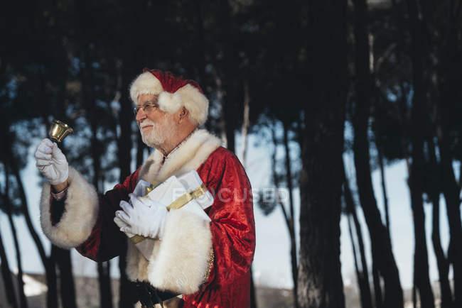 Веселий старший чоловік у костюмі Діда Мороза стояв з подарунком і дзвін у балакучих руках дивлячись на природу фону — стокове фото