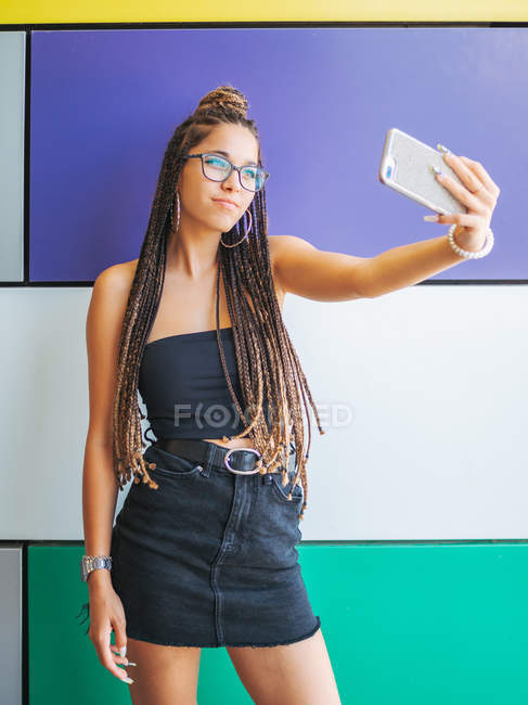 Pretty teenage girl with stylish dreadlocks taking selfie on smartphone in colorful room — Stockfoto