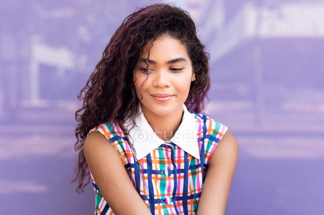 Portrait of charming young ethnic young woman with curly hair looking away against purple glass wall — Stock Photo