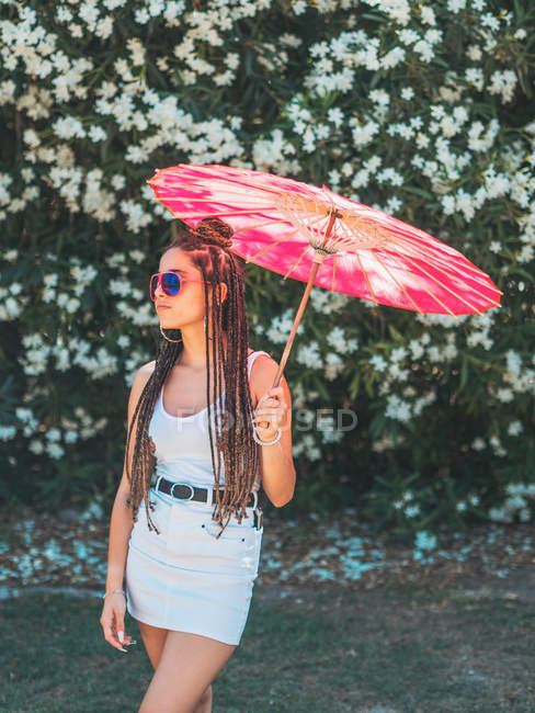Slim young woman in summer outfit and sunglasses with umbrella standing near blooming trees — Stock Photo