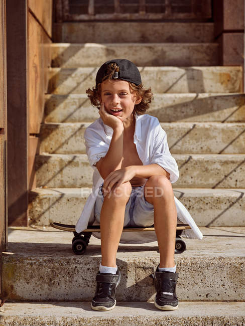 Cheerful boy sitting on skateboard on stairs in skatepark on sunny summer looking in camera — Stock Photo