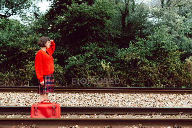 Woman with suitcase walking on railroad ties and looking at distance — Stockfoto