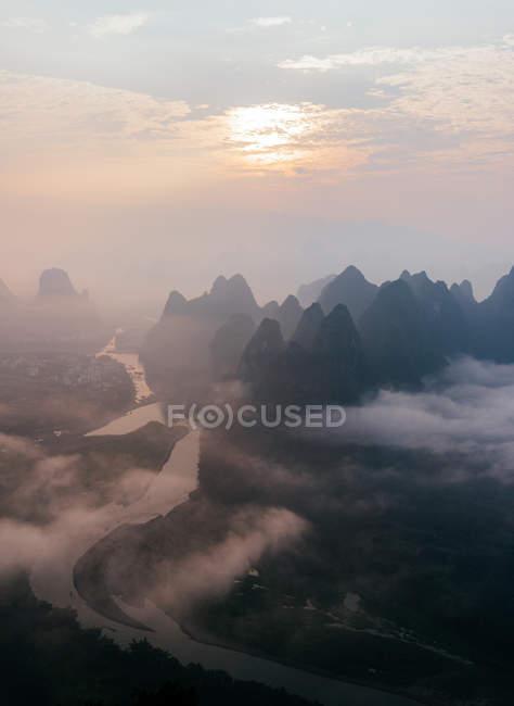 Vista aerea del fiume calmo e delle montagne rocciose scure nella nebbia mattutina con nuvole che scorrono sotto il cielo luminoso e il sole — Foto stock