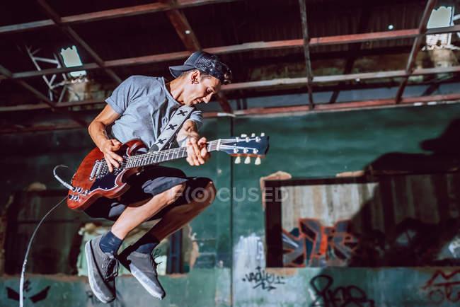Musicista che suona chitarra elettrica in luogo abbandonato — Foto stock