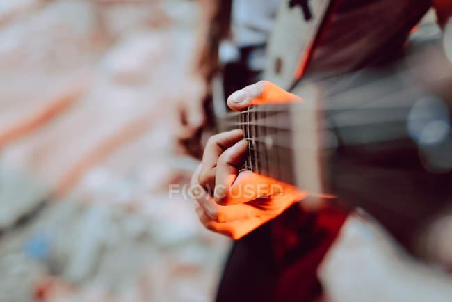 Weicher Fokus des männlichen Musikers, der beim Musizieren Saiten auf das Griffbrett der Gitarre spannt — Stockfoto
