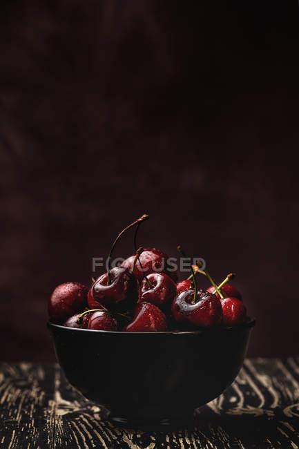 Смачні апетитно стиглі вишні в мисці на дерев'яній столі на темному фоні — стокове фото