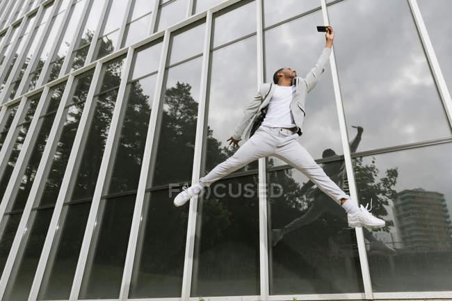Чернокожий мужчина прыгает, поднимая руку, как супергерой — стоковое фото