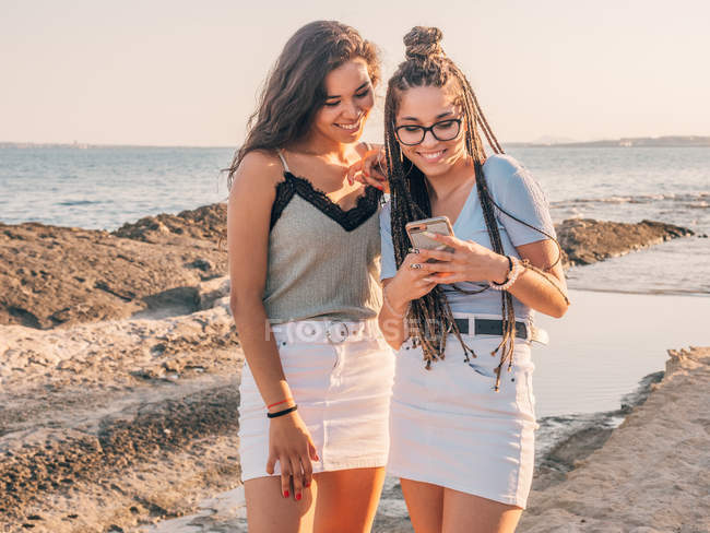 Smiling trendy young women using smartphone on beach — Stock Photo