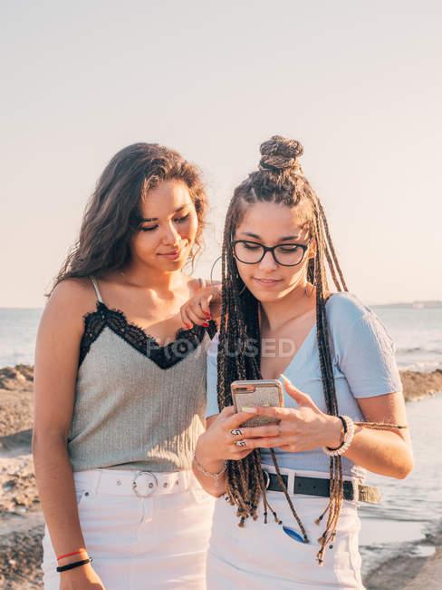 Giovani donne sorridenti alla moda che utilizzano lo smartphone sulla spiaggia — Foto stock