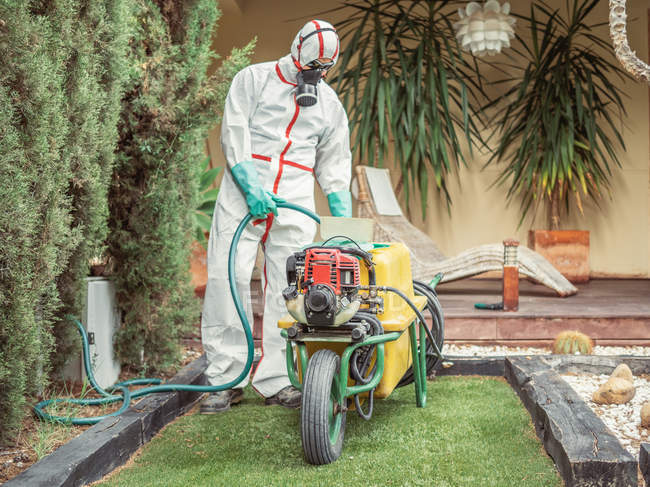 Fumigator pulling treatment hose from machine in yard — Stock Photo