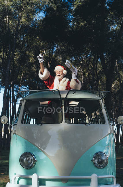 Cheerful senior man in costume of Santa Claus sitting in old van and waving hand from open window — Stock Photo