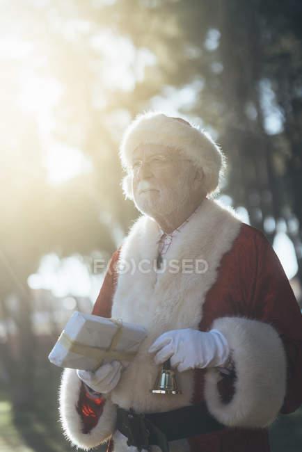 Вдумливий старший чоловік в костюмі Санта-Клауса, стоячи з подарунком і дзвіночок в любили руки на природу фону — стокове фото