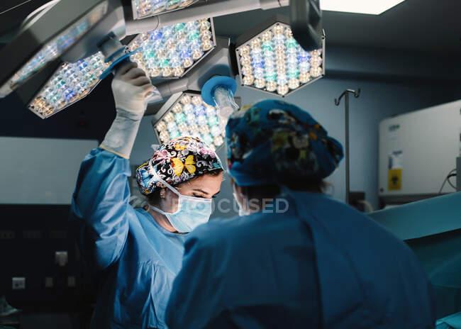 Ernsthafter junger Arzt in Schutzmaske und Mütze, der mit Instrumenten und Erntehelfer operiert — Stockfoto