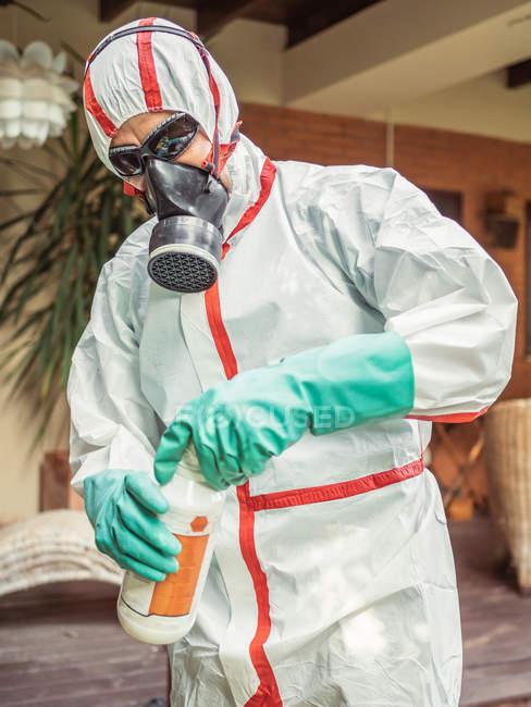 Mann im Anzug für Begasung gießt Chemikalie in Tank — Stockfoto