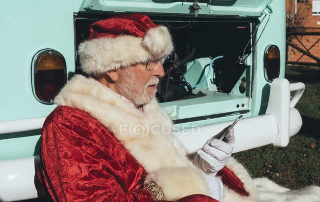Старший чоловік в костюмі Діда Мороза за допомогою мобільного телефону, сидячи в Ван з відкритим моторному відсіку — стокове фото