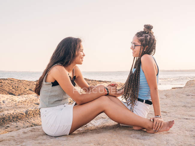 Smiling trendy young women relaxing on seashore — Stock Photo