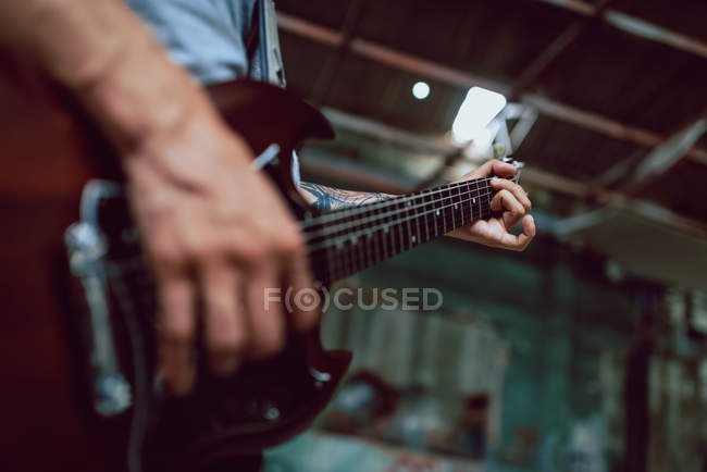 Man clamping strings on guitar neck — Stock Photo