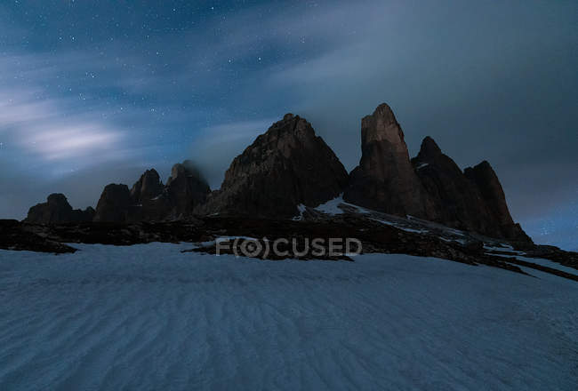 Gloomy cold landscape of rocky mountains in snow-white valley against magical starry sky in Dolomites, Italy — Stock Photo