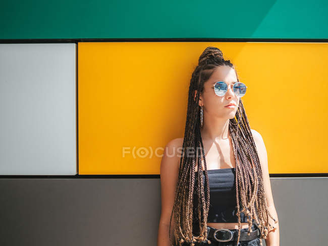 Pretty stylish teenage girl with unique dreadlocks looking away on colorful background — Photo de stock