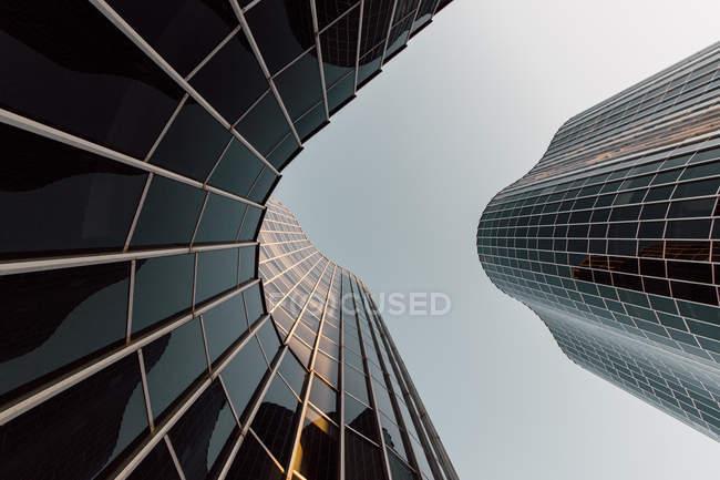 Desde abajo rascacielos geométricos con diseño futurista con ángulos redondos y paredes espejadas en Barcelona España - foto de stock