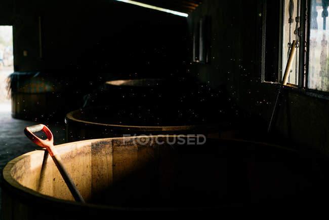 Barris de madeira usados vazios na luz solar no armazém rural velho escuro — Fotografia de Stock