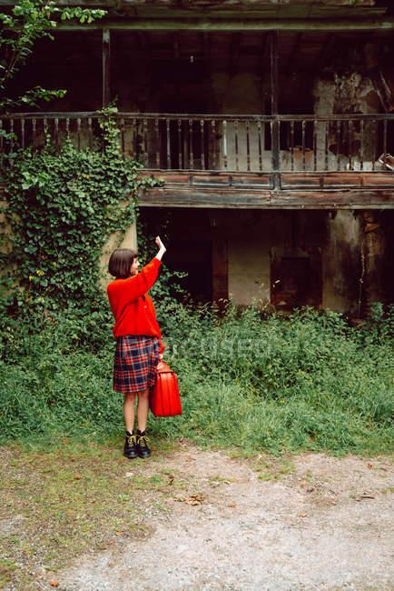 Femme en rouge avec grande valise rouge vintage debout en face de la maison abandonnée dans la campagne — Photo de stock