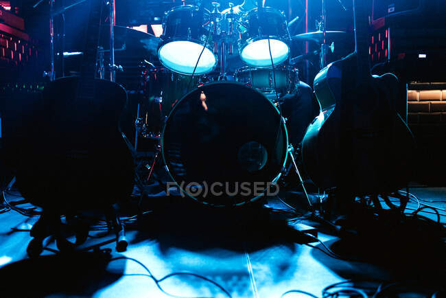 Large drum set with drums sticks and guitars on stage under blue neon light in anticipation of game — Stock Photo