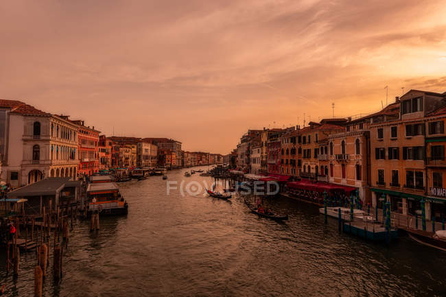 Grand canal passant entre les bâtiments au coucher du soleil — Photo de stock